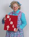 Rainbow the Clown holding an oversized Bible