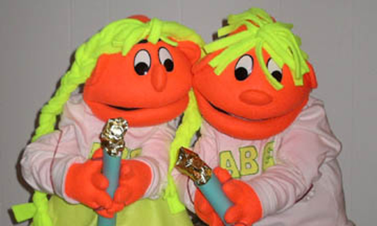 Two similarly-colored puppets holding candles