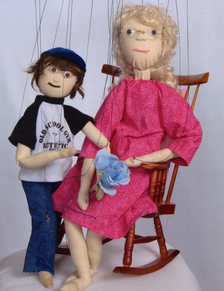 Two marionettes, one in a rocking chair