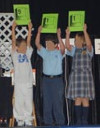 Three children hold up signs showing 9-1-1