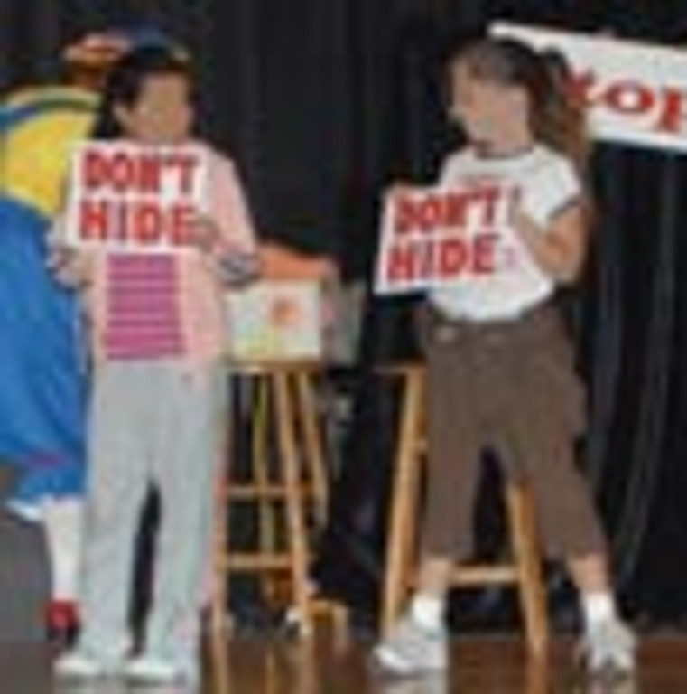 "Two children hold signs that say ""Don't Hide"""