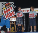"Rainbow and two children hold signs that say ""Don't Hide"""