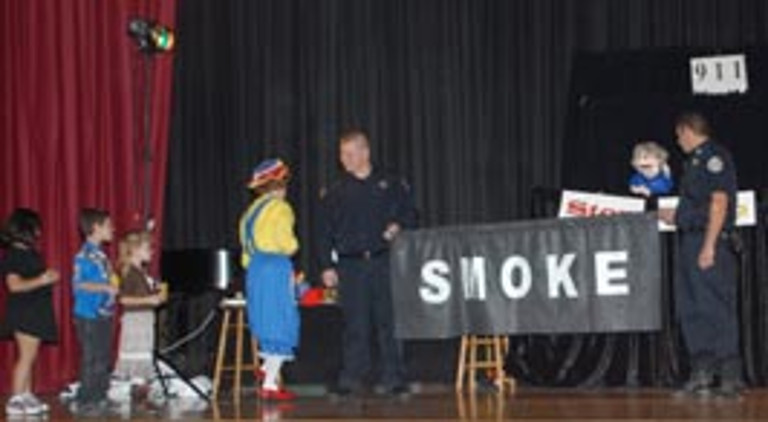 "Rainbow talks to a fire fighter holding a banner that reads ""smoke"""